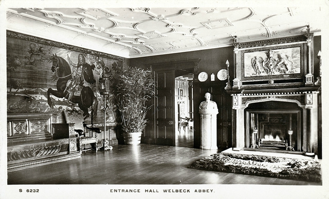 Old postcard of Welbeck Abbey's Entrance Hall. Instead of the tapestry on the left wall, there are now three horse paintings, a central table and a large rug.